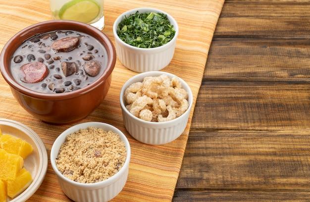 Feijoada tradicional brasileira com farinha de mandioca, couve, caipirinha