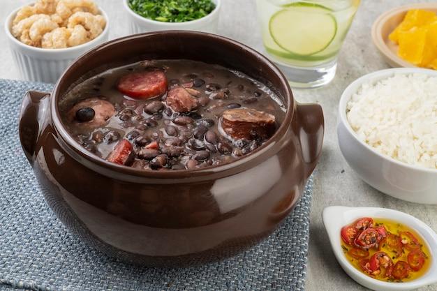 Feijoada tradicional com arroz, laranja, couve, torresmo, pimenta e caipirinha.