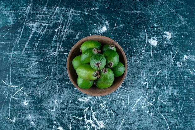 Feijoas em uma xícara de madeira sobre fundo azul. foto de alta qualidade