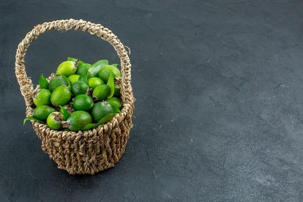 Feijoas frescas de vista frontal em uma cesta em superfície escura com espaço livre