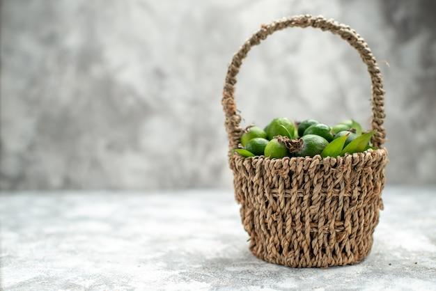 Feijoas frescas em uma cesta de vime em uma superfície cinza isolada no espaço livre