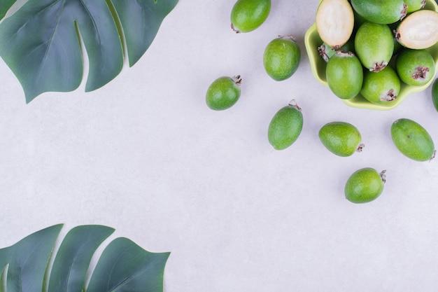 Feijoas verdes em uma xícara com folhas ao redor.