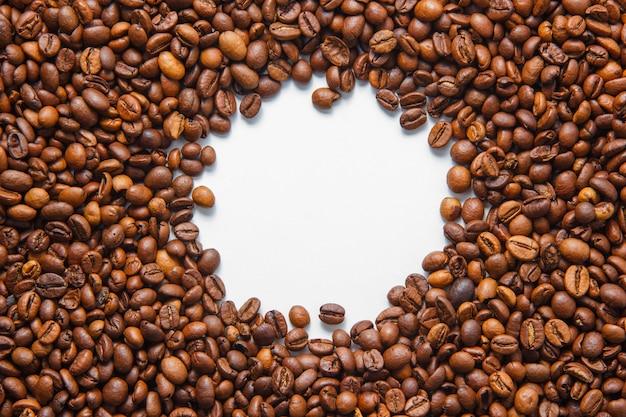 Feijões de café da vista superior no furo no centro no fundo branco. horizontal