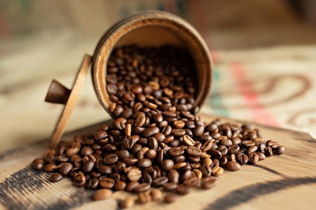 Feijões de café dispersados em uma placa de madeira. fechar-se