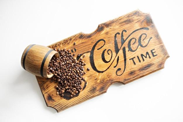 Feijões de café dispersados em uma placa de madeira.