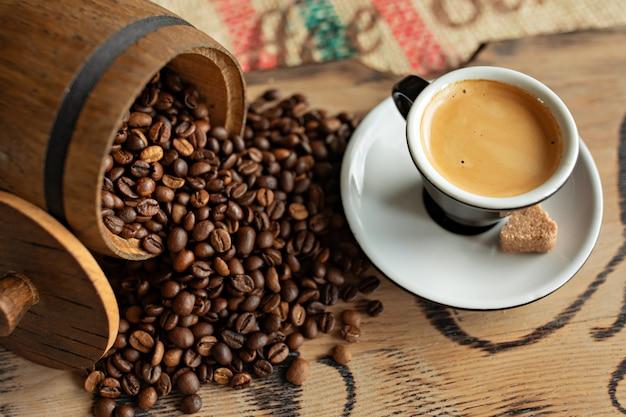 Feijões de café dispersados, um copo do café, partes de chocolate com porcas em uma placa de madeira.