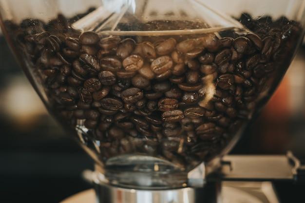 Feijões de café na máquina de café com tom da cor do vintage.