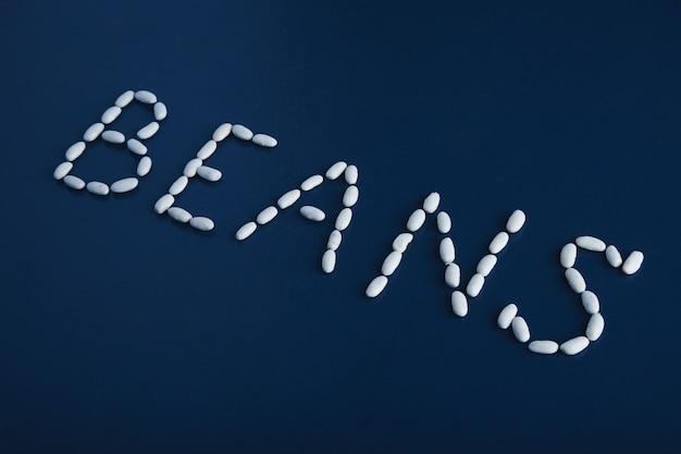 Feijões de palavras com vista lateral focada com letras com uma pilha de grãos brancos isolados na superfície da mesa azul rústica