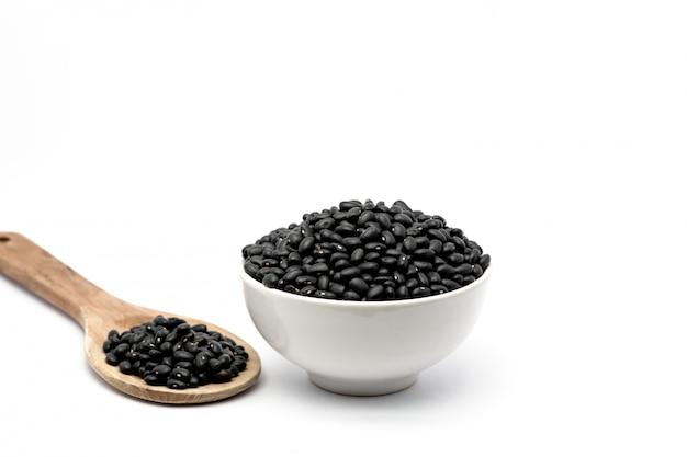 Feijões pretos naturais em uma bacia e em uma colher de madeira isoladas. feijão preto fornecendo nutrientes vitaminas e ferro.