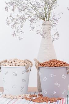 Feijões secos e ervilhas em baldes com flores.