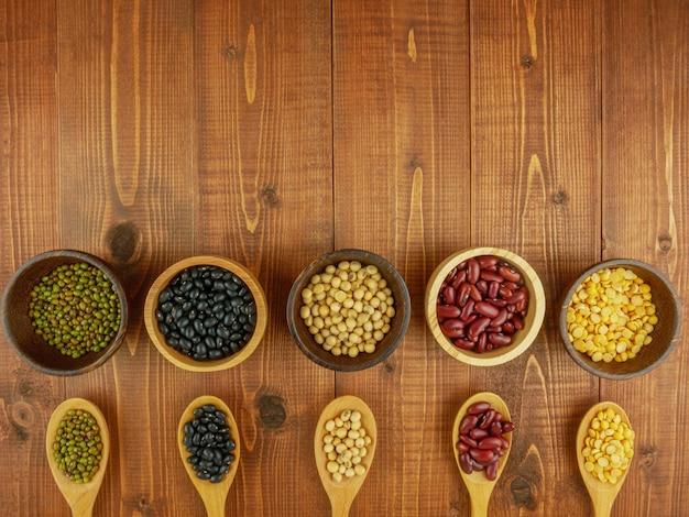 Feijões variados em taças na mesa de madeira