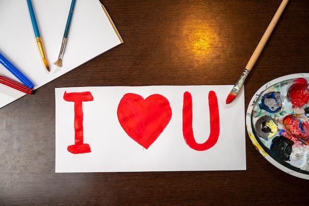 Feitas à mão cartão para dia dos namorados. amo-te sinal pintado com pincel em papel branco.