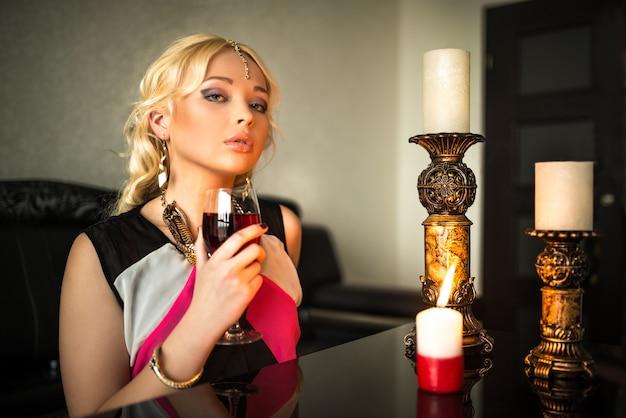 Feiticeira loira jovem simpática bebe vinho sentado a uma mesa rodeada de velas.