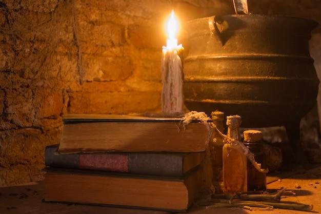 Feitiço da noite de bruxa com velas e pote com fogo entre teias de aranha e terra antiga