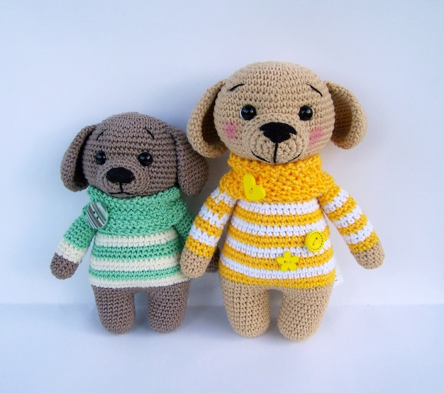 Feito a mão bonito faz crochê a boneca canino isolada no fundo branco com reflexão da sombra.