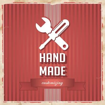 Feito à mão com o ícone da chave de fenda cruzada e chave inglesa e slogan sobre fundo vermelho listrado. conceito vintage em design plano.