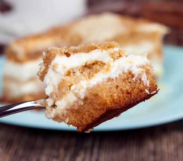 Feito com uma grande quantidade de ingredientes, um pedaço de bolo com um grande número de calorias para comer no final do almoço, pastelaria feita de bolo e creme, doce e deliciosa sobremesa de várias camadas