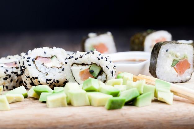 Feito de arroz e truta ou salmão com comida de sushi de vegetais, comida asiática de arroz e frutos do mar na mesa durante as refeições, comida asiática