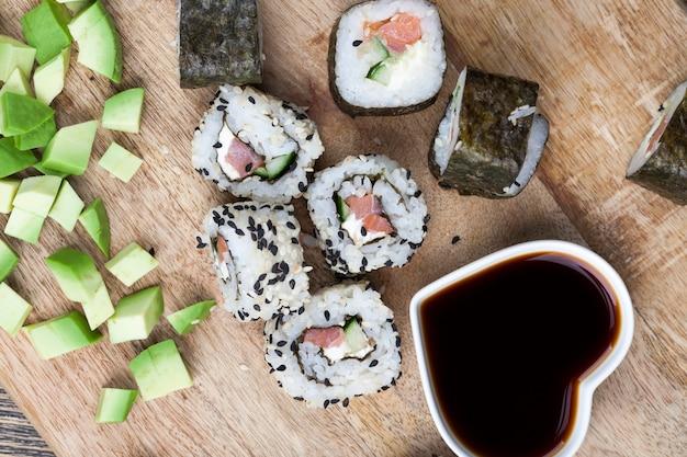 Feito de arroz e truta ou salmão com vegetais, comida de sushi com molho de soja, arroz asiático e frutos do mar na mesa durante as refeições, comida asiática e molho de soja