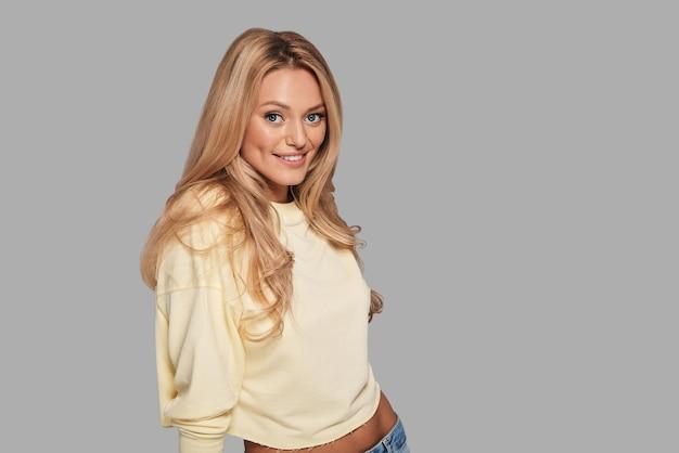 Feito para ser modelo. mulher jovem e bonita olhando para a câmera e sorrindo em pé contra um fundo cinza