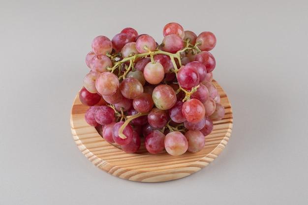 Feixe de cachos de uva em uma travessa no mármore