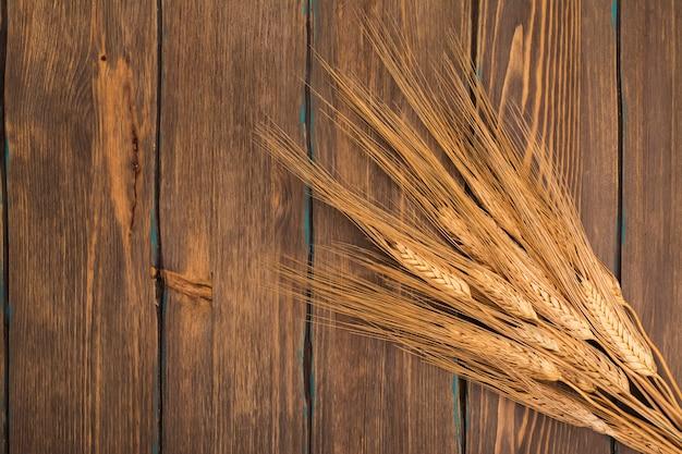 Feixe de espigas de trigo, sobre fundo de madeira. vista do topo