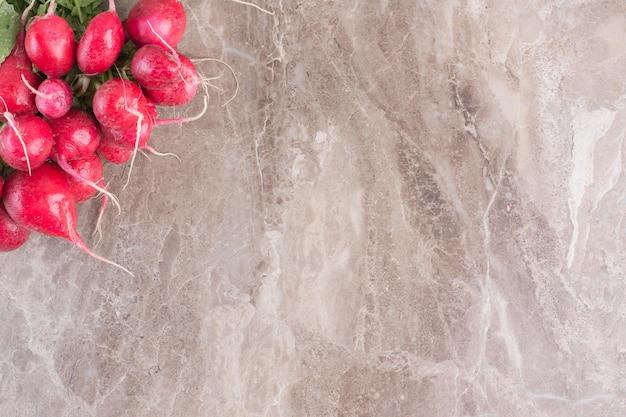 Feixe de nabos vermelhos na superfície de mármore