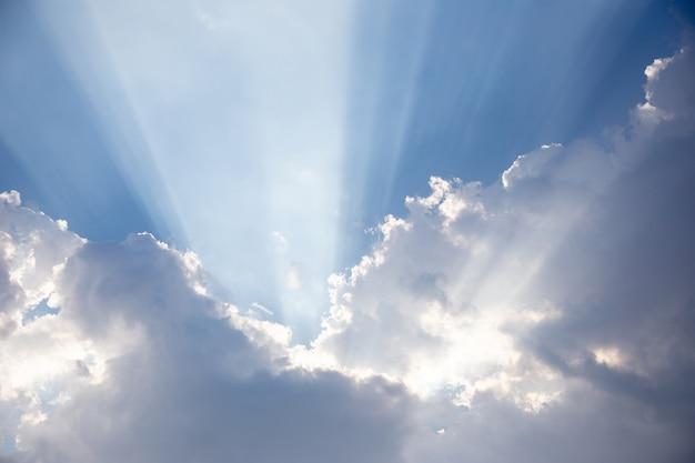 Feixe de sol lindo por trás da nuvem e céu azul
