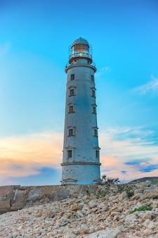 Feixe do holofote do farol pela brisa do mar à noite. vista do mar ao pôr do sol