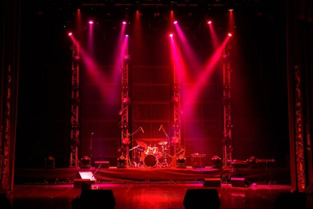 Feixes de luzes no palco com instrumentos musicais