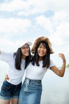 Felicidade alegre asiática de dois adolescentes na praia do mar de férias