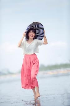 Felicidade asiática bonita da mulher mais nova na praia do mar das férias