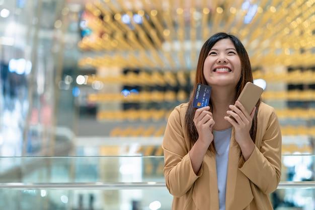 Felicidade asiática da mulher do retrato ao guardar o cartão de crédito e o telefone móvel para compras on-line na loja de departamentos