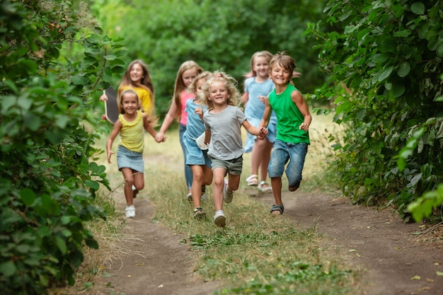 Felicidade. crianças, crianças correndo na floresta verde. alegres e felizes meninos e meninas brincando, rindo, correndo pelo prado verde florido. infância e verão, conceito de emoções sinceras.