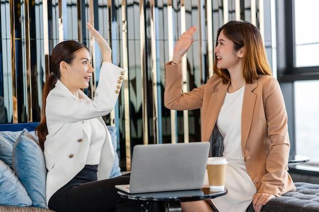 Felicidade de duas empresárias asiáticas comemorando juntas ao verificar a meta de sucesso