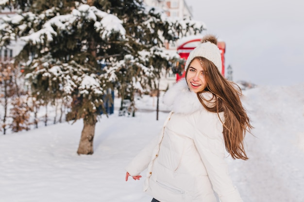 Felicidade de neve do inverno de alegre garota atraente com longos cabelos castanhos, andando na rua.