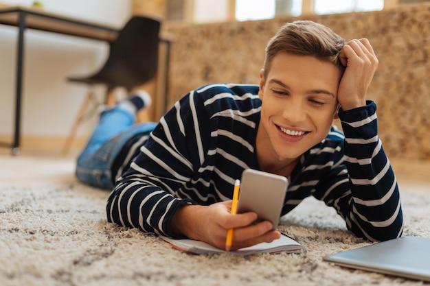 Felicidade dentro de mim. jovem bonito e alegre de cabelos louros deitado no chão, sorrindo e segurando seu telefone e um lápis