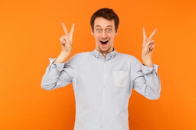 Felicidade do símbolo da paz, jovem adulto, mostrando o símbolo da paz para a câmera