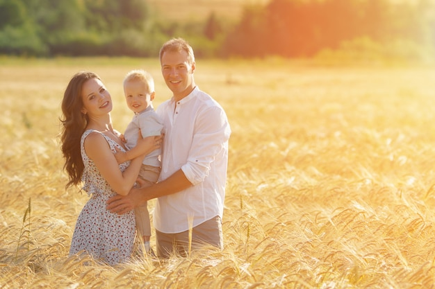 Felicidade dos pais, caminhando com a criança ao ar livre. lazer de mãe, pai e filho juntos no campo de trigo. luz solar
