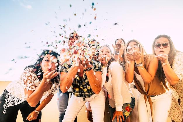 Felicidade e conceito alegre - comemora o grupo de mulheres felizes. todos juntos soprando confete e se divertindo