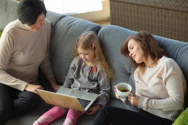 Felicidade. família amorosa feliz. avó, mãe e filha passando um tempo juntas. assistindo cinema, usando laptop, rindo. dia das mães, celebração, fim de semana, férias e conceito de infância.