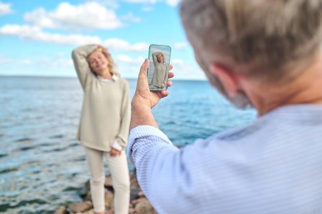 Felicidade. homem de pé, de costas para a câmera, segurando o smartphone com o foco em uma mulher de meia-idade, muito feliz, posando perto da água em um dia ensolarado