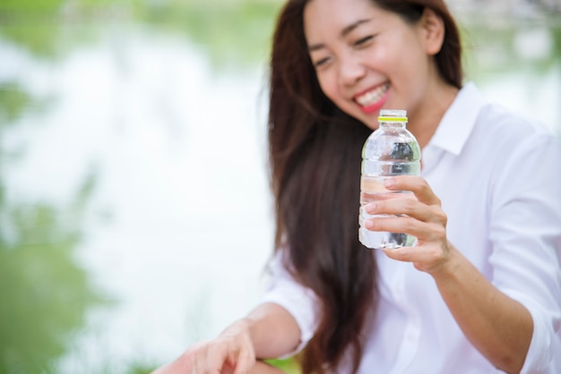 Felicidade. lindas mulheres chinesas asiáticas segurando uma garrafa de água mineral, felizes e sorrindo