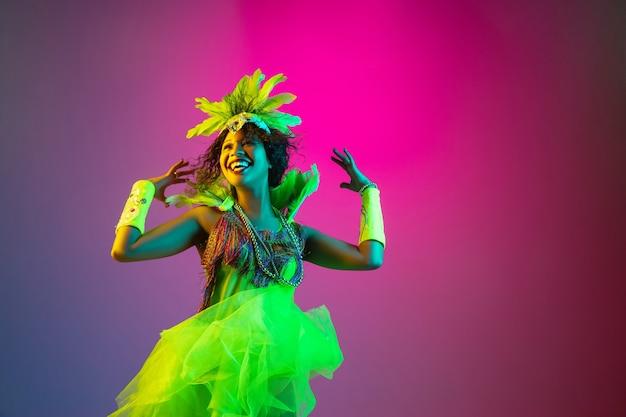 Felicidade. mulher jovem e bonita no carnaval, elegante traje de máscaras com penas dançando na parede gradiente em luz de néon. conceito de celebração de feriados, festa, dança, festa, se divertindo.