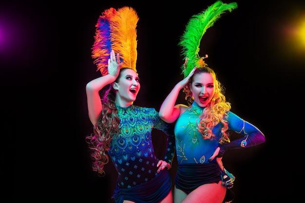 Felicidade. mulheres bonitas no carnaval, elegante traje de máscaras com penas em fundo preto em luz de néon. copyspace para anúncio. celebração de feriados, dança, moda. época festiva, festa.
