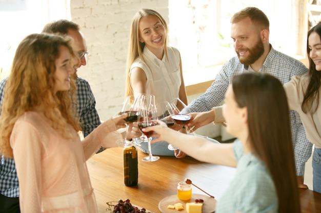 Felicidade. pessoas tilintando taças com vinho ou champanhe.