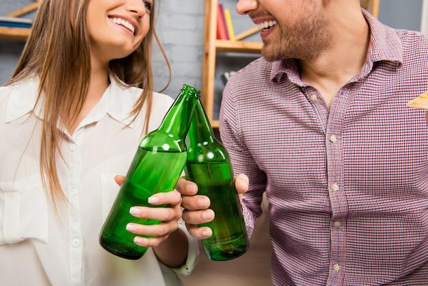 Felicidades! feche o retrato de um homem e uma mulher bebendo cerveja