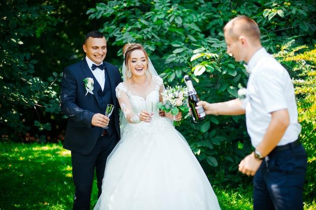 Felicidades! recém-casados com amigos bebem champanhe ao ar livre. as pessoas celebram e levantam taças de vinho para brindar.