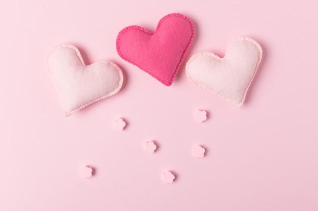 Felicitações cor-de-rosa do dia de valentim ou triângulo de amor no fundo pastel com brinquedos feitos à mão.
