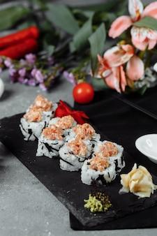 Felix roll com molho de wasabi de atum e gengibre em conserva em um quadro negro